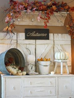 Distressed shutters and shelves make great backdrops and ledges for faux fall leaves and other autumn-inspired decor. Design by Ruth Winans