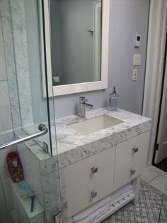 """Perfect 10 Design. Small Bathrooms need custom solutions.  Narrow RH inspired vanity  built for a small sink.  Wrapping marble down vanity to save space for shower glass.  Doors built to look like drawers save costs.  A small ledge hides personal items in shower.  Carrara & Dolomite create contrast.  A tile """"carpet"""" of Carrara flowers, brick edging, & Dolomite trim. http://www.restorationhardware.com/catalog/product/product.jsp?productId=prod1419092&categoryId=cat2520056"""