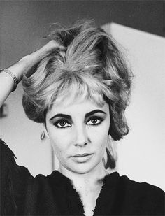 Elizabeth Taylor trying on a blonde wig for a portrait session in 1963