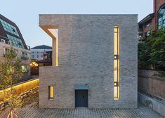 Cut-aways in the brick facade of this family home by OBBA provide views over a small walled garden in the city's high-density Gangnam neighbourhood