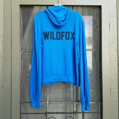 """{Wildfox} """"Classic Fox"""" Malibu zip. This cerulean blue is one of the loveliest colors they have ever used. This hoodie is well-loved, I bought it secondhand a few months ago, wore it a few times, washed it on delicate and flat-dried.  Graphic shows typical fading, the banding has relaxed a bit at the waist and cuffs, and it is less soft than new, but still an amazing weekend warrior hoodie. No staining, no tears, no holes.  Tagged small, this fits everyone from extra-small through perhaps…"""