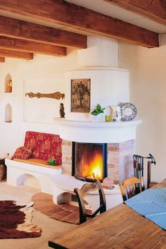 Richtig urig und gemütlich ist es in in diesem Landhaus mit dem runden Kamin von BRUNNER und der Holzmöblierung. Die schöne Ofenbank lädt zum Verweilen und Aufwärmen ein. Home Fireplace, Brick Fireplace, Passive Solar Homes, Solar House, Earth Homes, Natural Building, Exposed Beams, Spanish Style, Tiny House