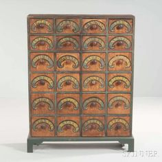 """Paint-decorated Spice Cabinet, New England, early 19th century, the blue dovetail-constructed case of twenty-four drawers with blue scrolls and lettered in yellow """"PEPPER,"""" """"CLOVES,"""" """"NUTMEG,"""" and more, all on a putty painted ground (restoration), ht. 48 1/2, wd. 36 3/4, dp. 10 1/4 in."""
