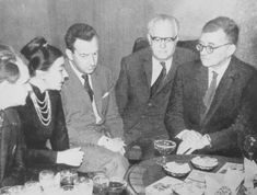 Benjamin Britten and Dmitri Shostakovich having a miserable time at a party with some friends.