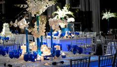 Monaco blue, cobalt glasses, vases, votives against white orchids. By Diana Gould, Ltd.