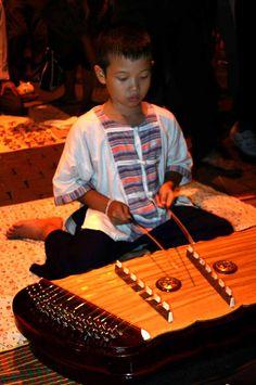 A boy playing a khim (hammered dulcimer) Thailand