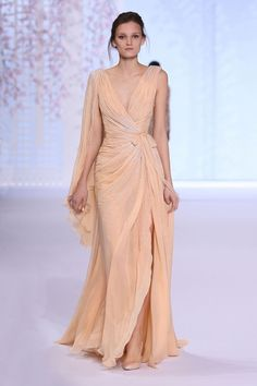 Apricot silk chiffon draped gown with asymmetric sash and glass bead embroidery.