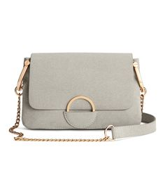 Check this out! Small shoulder bag in regenerated leather with a narrow metal chain shoulder strap, decorative metal ring on flap, magnetic fastener, and two compartments. Lined. Size 1 1/2 x 5 x 8 1/4 in. - Visit hm.com to see more.