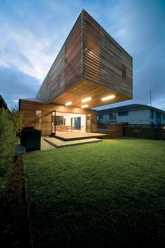 Drilled wood facade with windows behind, large cantilevered volume, linear lighting | Jackson Clements Burrows Architects | Melbourne, Australia
