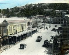 The photograph shows Hastings Street, Napier taken after the devastating earthquake and subsequent fire of 3 February 1931. The debris from the damaged buildings has been removed and the land cleared. Rebuilding of shops and business premises has begun. The buildings from left to right are Ritchies, Harstons Limited and Ringland Brothers (Bros). The tram line is still present as part of the road. The beginning of Shakespeare Street can be seen. Photographer, unknown. Date, 1932.