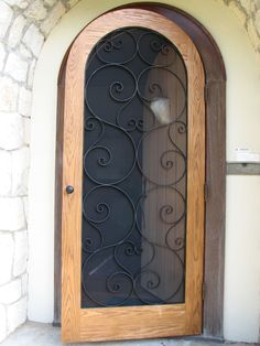 A screen door is a must for buggy climates, but take yours the extra step by buying one that's particularly lovely. We adore the swirling iron framework and Arched Doors, Windows And Doors, Porches, Portal, Metal Screen Doors, Door Images, Entrance Decor, Front Door Design, Window Screens