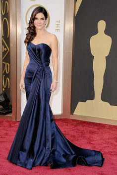 Sandra Bullock defies gravity on the red carpet. . . this figure-flattering, strapless, royal blue gown by Alexander McQueen is a perfect contrast to her complexion, while creating a long, lean silhouette.  Hair and make-up are perfect. . . soft and feminine.  #alexandermcqueen #lorraineschwartz #sandrabullock