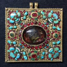 Gilt copper gau, Tibetan, inset turquoise, gemstones, mother of pearl, crystal cabochon in centre with carving of  avalokitesvara. Private collection