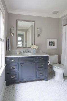 Blue and gray bathroom features walls painted gray, Farrow & Ball Cornforth, lined with a blue grey vanity painted Benjamin Moore French Beret topped with Italian white carrera marble under a silver leaf beveled mirror illuminated by mirrored sconces alongside a carrera hex floor,.