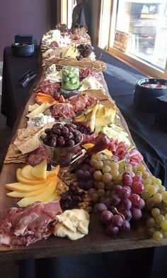 A fruit, cheese, meat, and cracker smorgasbord table