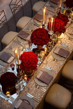 <p>The bead-rimmed chargers are set on a metallic two-tone tablecloth, and a mirror runner divides the middle of the table, set with candles in silver and glass holders and bunches of lush red blooms.</p><p><i>(Photo: Colin Miller)</i></p>