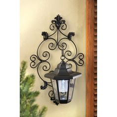 Delicate scrollwork wall plate and classic lamp make a gracious addition to your outdoor living space; hidden solar collectors store sunlight for plentiful after-dark illumination. The perfect fusion of smart energy savings and old fashioned charm!