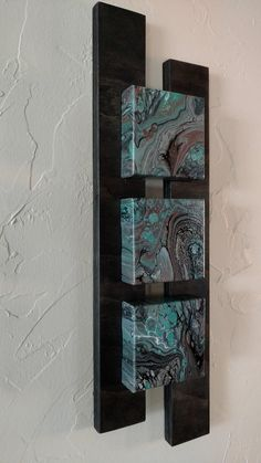 One of a kind! Acrylic pour painting on 4 x 4 x 1 canvas blocks. The blocks are inset 1/4 in stained 3/4 plywood 2 piece custom frame. Overall dimensions: 22 x 6 1/2 x 1 7/8 Canvas is finished with gloss varnish - wood with matte. Colors spotlight turquoise, black and gray with splashes