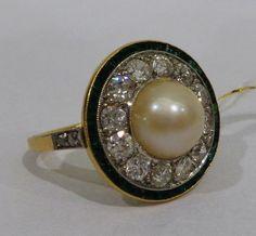 Anel francês em ouro com esmeraldas, brilhantes e pérola central pesando 4,8 gramas de peso total.