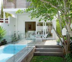 une mini piscine coque hors terre bordée d'une plage de piscine en bois et des garde-corps en verre