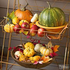Fill a wire tiered plant stand on your porch to display your fresh fall finds, such as apples, foilage, pumpkins, and other gourds. Wooden bowls and vintage crocks add interest to the outdoor pumpkin decoration./