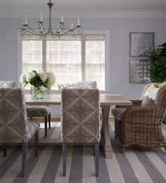 Dining room with a striped grey and white rug, upholstered chairs around a farmhouse style table with a wicker armchair at the head of the table Side chair fabric