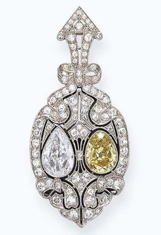 A BELLE EPOQUE COLORED DIAMOND BROOCH. Centring upon a pear-shaped yellow diamond and diamond, set within an old European and single-cut diamond openwork pierced plaque, enhanced by ribbon motifs, with a black onyx backing, mounted in platinum, circa 1910.