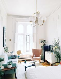 With the high ceilings, moldings and that window the space is full of glamorous antique charm. With a clever layout and personal touches, Lauren has played up all of the best aspects of the space, creating a sun-drenched dream that looks for bigger than its 500 feet.