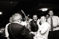 At a fun wedding held at The Addison, Boca Raton, a wedding guest jams on his air guitar with the guitarist for the John Parker Band, whose dark suit and sunglasses add to the party's fun, cool vibe. The newlyweds and their guests danced all night long to the band's music! http://www.jpband.com/weddings.html