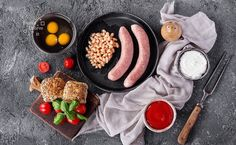 English Breakfast with sausage - English Breakfast: raw sausage with beans  and tomatoes, a metal frying pan decorated with fresh herbs.