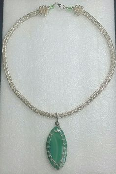 Silver viking knit necklace with silver spiral end caps and a silver viking knit wrapped green agate stone.