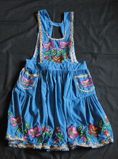 Apron Oaxaca Mandil Mexico    The Zapotec women who live in San Miguel del Valle, Oaxaca are known for their beautiful aprons embroidered with colorful flowers. The aprons are made by women in this community, and are worn over a dress.