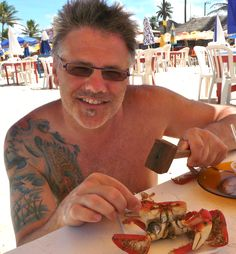 Dan Trepanier cracking open crab for lunch at the beach in Aracaju Brazil - Photo by Ernani Oliveira