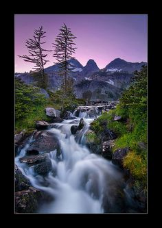 An outlet stream pours from Lower Ice Lake, beginning its 1500-ft cascade into a valley far below - Glacier Peak Wilderness, Washington;  photo by Michael Bollino, via Flickr