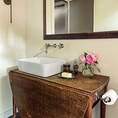 An old drop leaf table adds a surprising element to this quaint master bath.