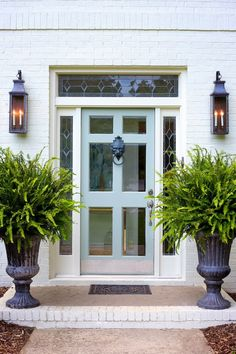 Great Curb Appeal - Front entry with lass and wood painted front door, white brick, sconces and potted plants. Exterior Design, Beautiful Doors, Door Planter, Front Door Decor, Front Door, Door Color, Doors, Exterior Doors, House Exterior