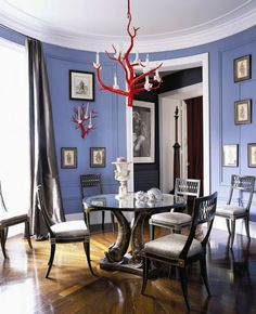 Periwinkle blue walls in a circular Paris dining room, love the coral chandelier! and the fish table......