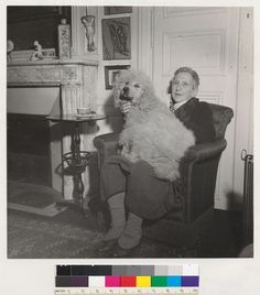 [Gertrude Stein in her home at rue Christine with her poodle on her lap.]