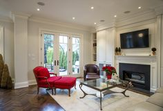 Chevron-patterned dark hardwood flooring underpins this white toned living room, with a bold red traditional carved wood chair, leather armchair, glass coffee table, and beige sofa standing before a black marble fireplace with white mantle.