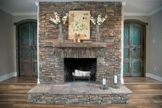 The fireplace is flanked by twin arched wood doors, painted blue-green and distressed.The fireplace is resurfaced in dry stack stone, replacing a standard brick hearth and surround.