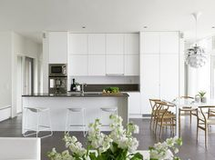A clean white contemporary kitchen with wood details and green plants. Classic. Timeless. Interior design.