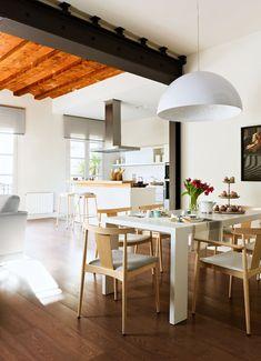 Comedor diáfano  Una viga vista pintada de negro y de aire industrial sirve de separación visual entre el comedor y el salón y la cocina.
