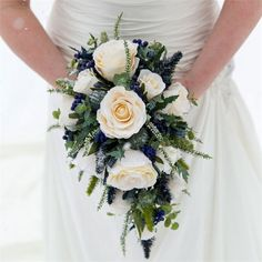 Noreen's wedding bouquet continued the Scottish theme, as she carried an arrangement of ivory roses, thistles, sea holly and heather, with blue tartan ribbon entwined throughout it.The bride opted for artificial flowers so she was able to get them in the UK and transport them to Canada and back easily. Deborah Nash of Hayling Florist created the stunning cascade bouquet, and also provided a pretty floral cake topper too.