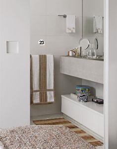 No banheiro, a porta de correr com puxador cavado substituiu o modelo de abertura normal e o armário embaixo da bancada deixa um nicho para apoiar cestos e revistas