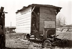 A one-room hut houses a family of nine in an open field between Camden and Bruceton, Tennessee, near the Tennessee River. The hut was built over the chassis of an abandoned Ford. Photograph by Carl Mydans, 1936. View full size.