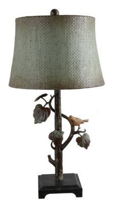 Woodstock Lamp Metal table lamp in vintage finish and Laurel Green hang-up with winding textured branch and antiqued yellow bird on worn black brown base. Hand-painted and aged woven bell shade