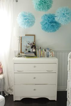 Beautiful vignette with white vintage chest, beadboard, light gray walls paint color, white window panels curtains and blue pom poms.