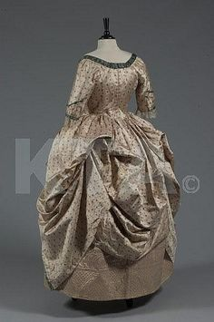 A brocaded silk open robe a la polonaise, circa 1785-90, of figured oyster silk woven with small floral sprigs, edged in peacock-green satin, the closed-front bodice with pointed low waist, single bone to fitted centre-back; together with a pale quilted pale pink silk petticoat adorned with quatrefoils and scrolls,