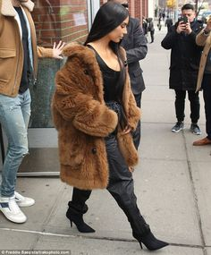 Her tricks pay off: Kim has a propensity for letting her jackets and coats fall off her to show off her chest. But she might be on to something as she is one of the most photographed women in the world