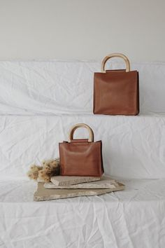 The Agnes Grande Bag is inspired by the minimalist french chic. A simplistic and stylish go to. leather with Natural Teak wood handles and square base. W x H x D Handle drop - Photography Bags, Fashion Photography, Minimalist Bag, Photo Bag, Leather Workshop, French Chic Fashion, Looks Style, Instagram Banner, Backpacks